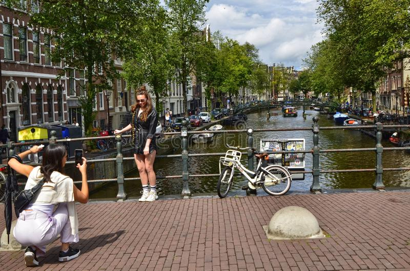 Amsterdam, Holland. August 2019. The bridges on the canals are a must for souvenir photos. A couple of women take a picture: one. Is posed and the other takes royalty free stock images