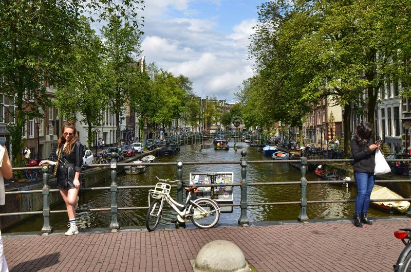 Amsterdam, Holland. August 2019. The bridges on the canals are a must for souvenir photos. A couple of women take a picture: one. Is posed and the other takes stock photo