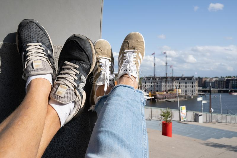 Amsterdam, Holland - August 2019: Couple relaxing on a modern design bench in NEMO Science museum Amsterdam rooftop park with a stock photography