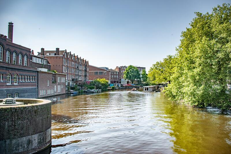 Amsterdam in Holland with its magnificent brunch breakfast canals, its levi barge bridge and traditional boat, flowery city bike. Amsterdam in Holland with its stock photos