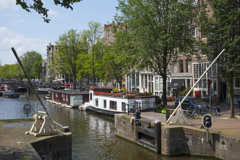 Boat lock on the Korte Prinsengracht and houseboat with flowers. Amsterdam, Holland - June 22, 2019:  Boat lock on the Korte Prinsengracht and houseboat with stock images