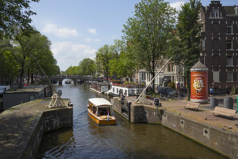 Boat lock on the Korte Prinsengracht and houseboat with flowers. Amsterdam, Holland - June 22, 2019:  Boat lock on the Korte Prinsengracht and houseboat with royalty free stock photo