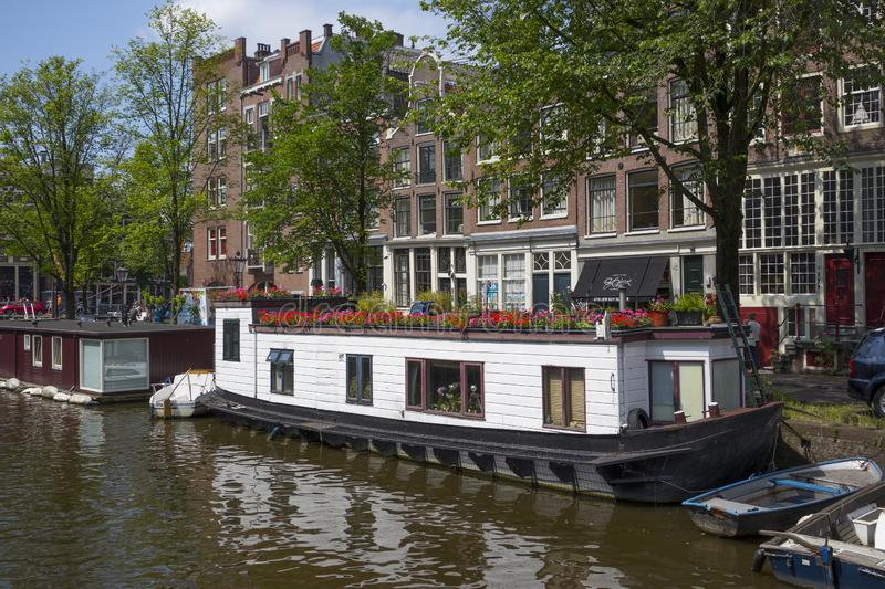 Houseboat with flowers on the canal at the Korte Prinsengracht. Amsterdam, Holland - June 22, 2019: Houseboat with flowers on the canal at the Korte stock image
