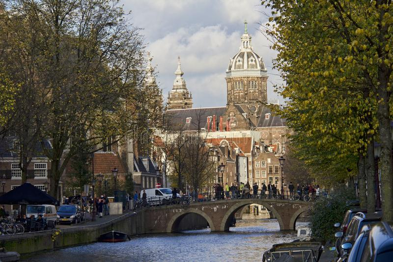 Amsterdam Church in Autumn. Amsterdam, Holland - November 12, 2015: People walk on bridge over a canal in autumn with Saint Nicholas Church in the background on royalty free stock images