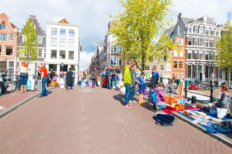 AMSTERDAM, HOLLANDES 27 AVRIL : Les personnes locales montrent leurs choses à vendre le jour du ` s de roi le 27 avril 2015 à Ams photo stock