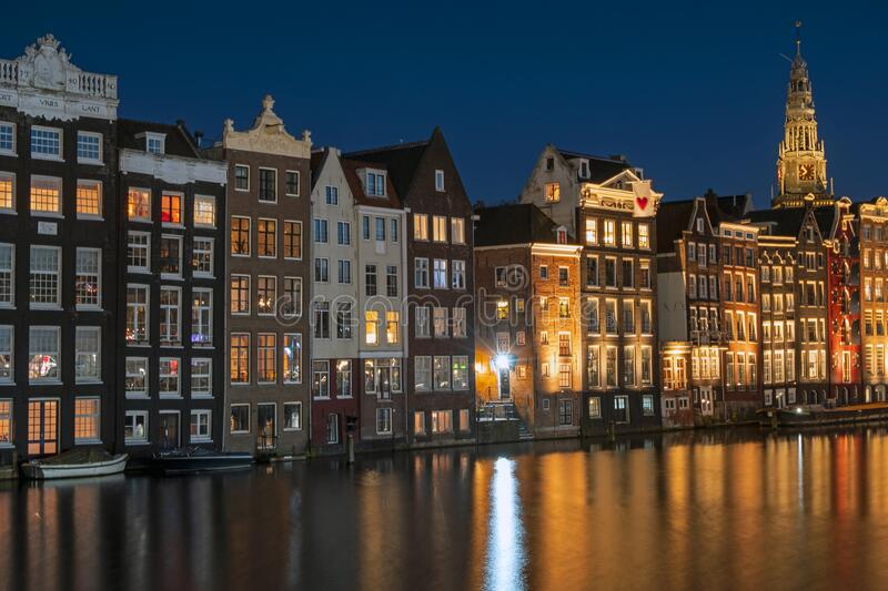 Amsterdam houses along the Damrak in the Netherlands at night royalty free stock photo