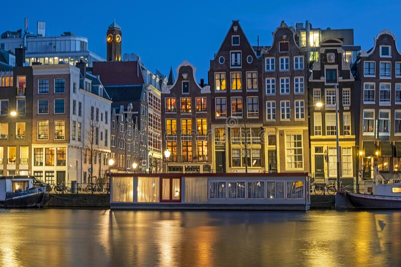 Amsterdam houses and house boats along the Amstel in Amsterdam the Netherlands at sunset royalty free stock photography