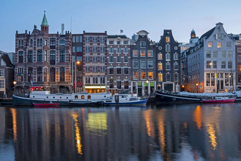 Amsterdam houses and house boats along the Amstel in Amsterdam the Netherlands at sunset stock images