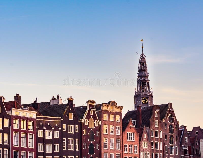 Amsterdam hus med färgrika fasader och Westerkerk kyrkligt torn under solnedgång på den Amstel flodkanalen i Amsterdam royaltyfri foto