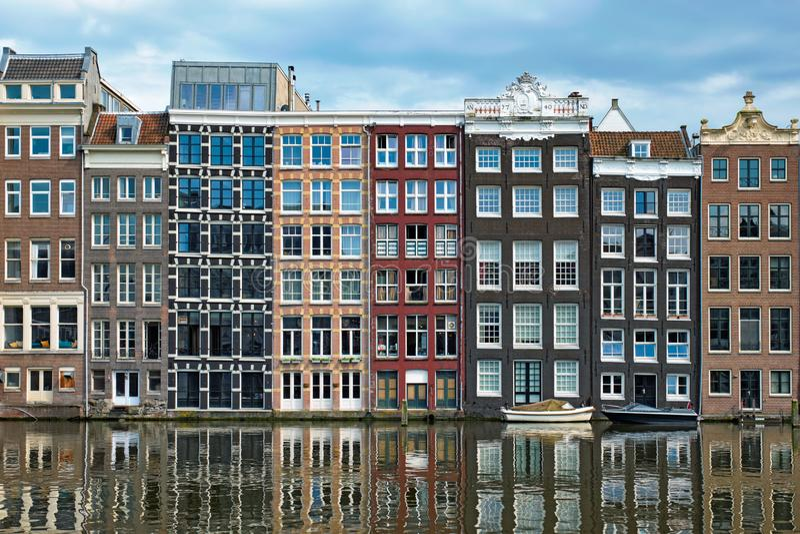 Amsterdam kanal Damrak med hus, Nederländerna arkivfoto