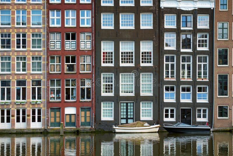 Amsterdam kanal Damrak med hus, Nederländerna royaltyfri foto