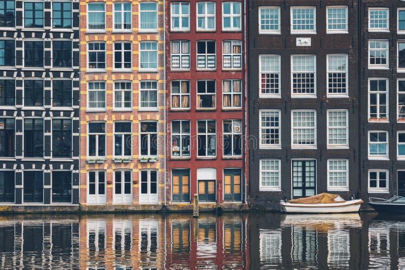 Amsterdam kanal Damrak med hus, Nederländerna royaltyfri fotografi
