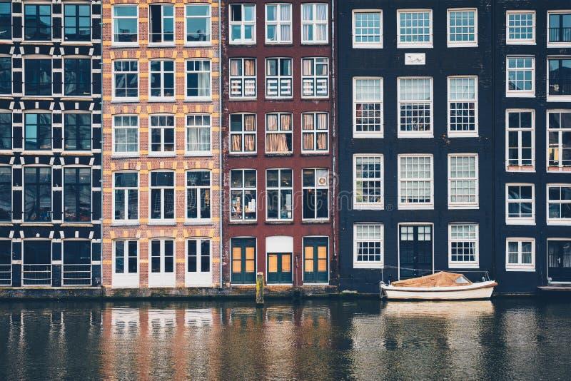 Amsterdam kanal Damrak med hus, Nederländerna arkivbilder