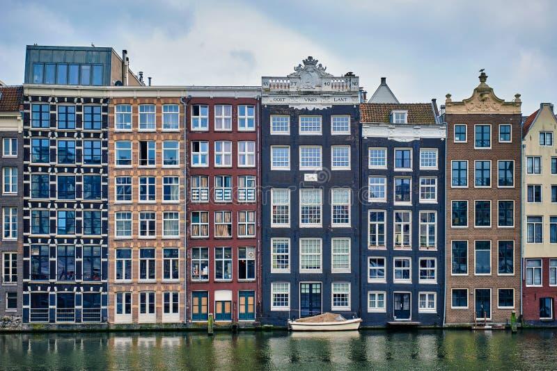 Amsterdam kanal Damrak med hus, Nederländerna royaltyfria bilder