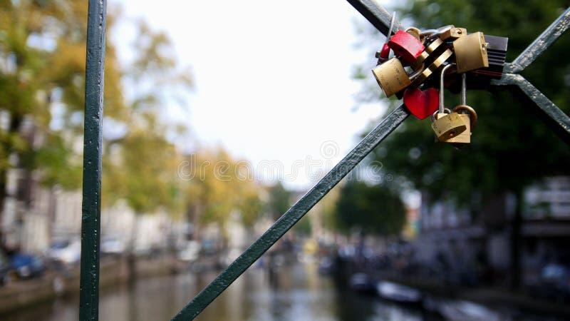 Amsterdam kanal, Holland, Nederländerna - sikten från bron som gifta sig låser arkivfoton