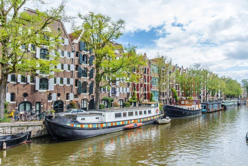 Amsterdam kanal med husbåtar och rad av klassiska arkitekturhus fotografering för bildbyråer