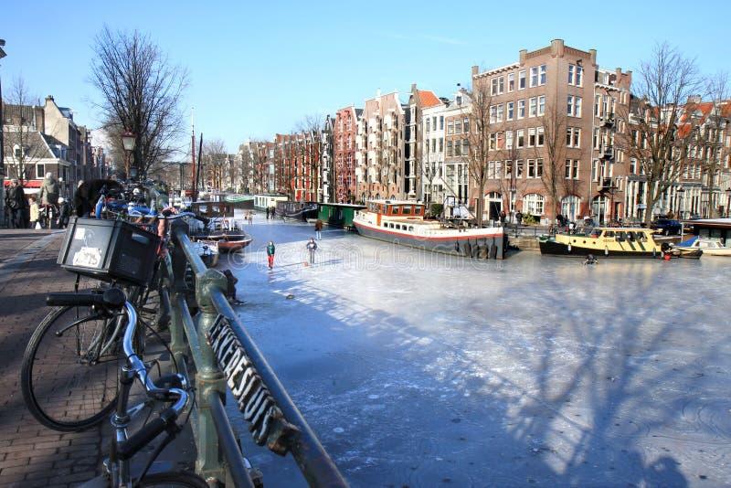 amsterdam kanalholländare som frysas över att gå royaltyfri fotografi