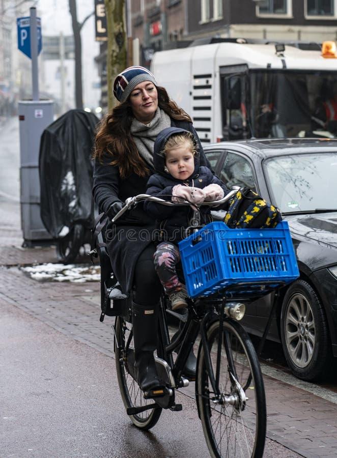 Amsterdam kobieta z jego synem w bicyklu obraz royalty free