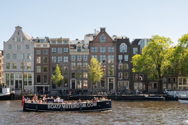 Amsterdam, los Países Bajos, mayo de 2018: Costa del río de Amstel en un día soleado con las casas y los barcos típicos a lo larg foto de archivo libre de regalías