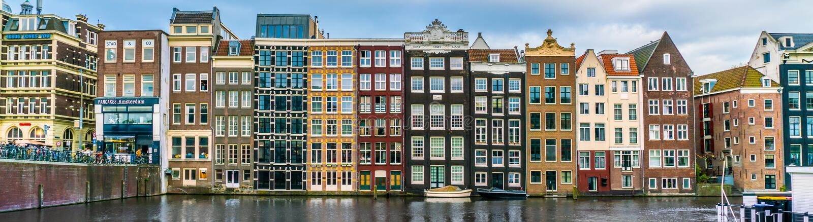 A row of old traditional houses at the Damrak in the center of town royalty free stock image