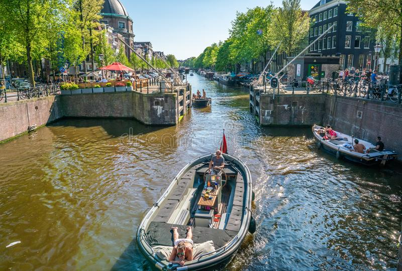 Amsterdam, May 7 2018 - small boat with locals passing the lock stock photography