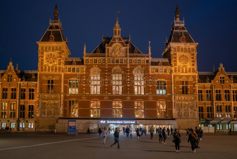 Travelers leaving and entering the Central train station of Amsterdam at night royalty free stock image