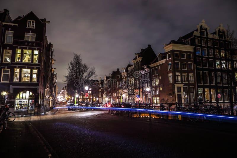 Amsterdam miasta nocy ulicy z różnymi rodzajami rusza się transport & sylwetki passersby zdjęcie stock