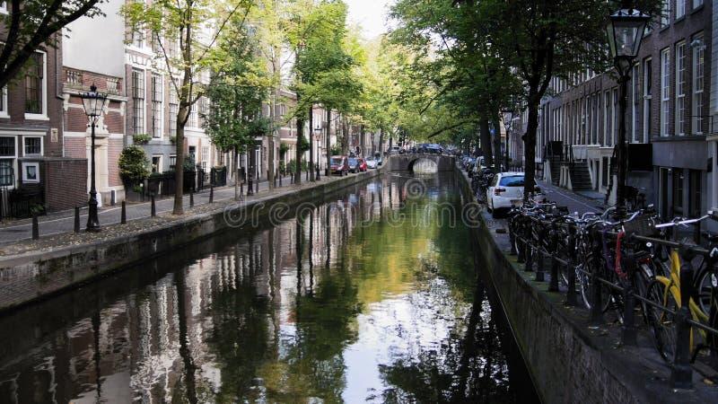 Amsterdam morgon i mittstaden - gata med cyklar och bilar på kanalen, höst, Nederländerna royaltyfri foto