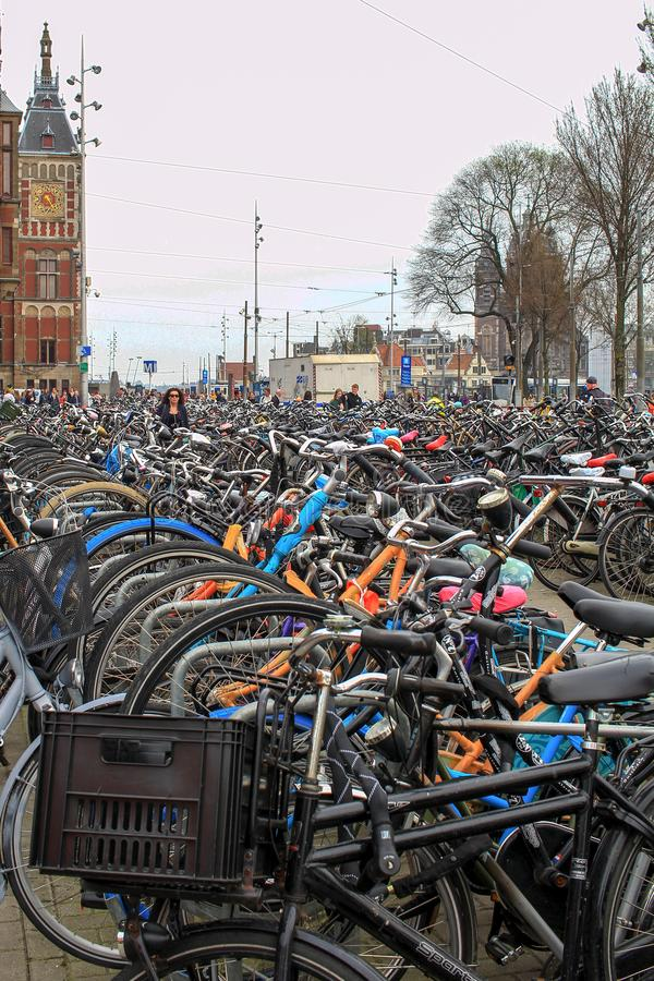 Amsterdam Nederländerna - April 10, 2018: Cykelparkering nära den centrala järnvägsstationen i Amsterdam Nederländerna royaltyfria bilder