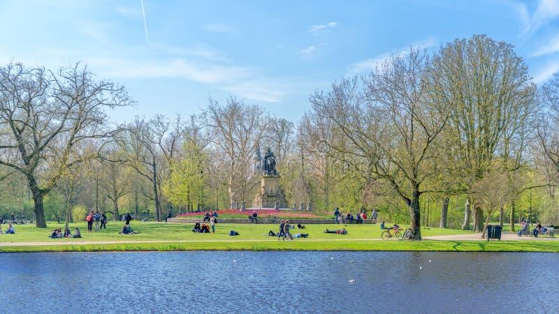 Amsterdam Nederländerna - April 9, 2019: Vondelpark som ett favorit- ställe för vilar och gå invånare och turister Parkera har arkivbild