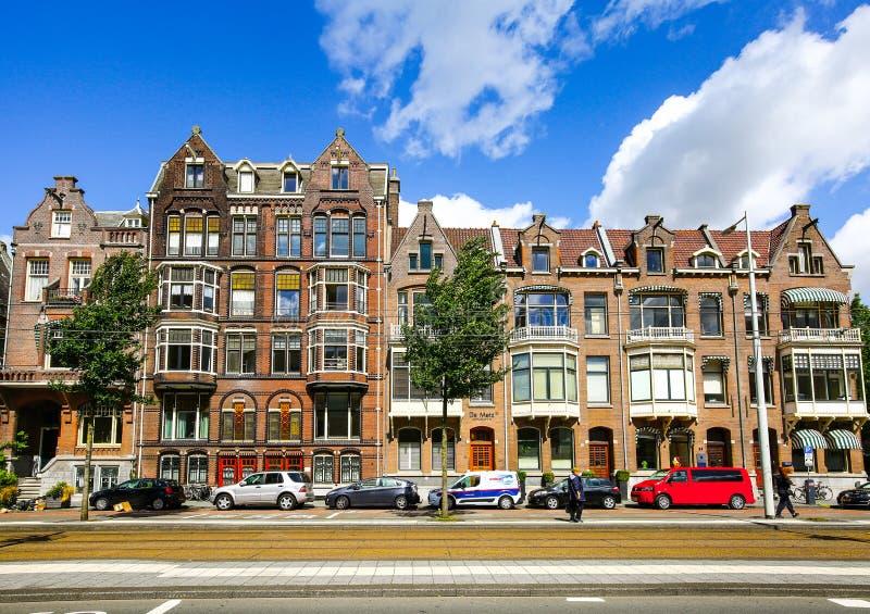 AMSTERDAM NEDERLÄNDERNA - AUGUSTI 3, 2017: Traditionellt holländskt hus, bilar och folk på gatan touristic säsong för sommar royaltyfri bild