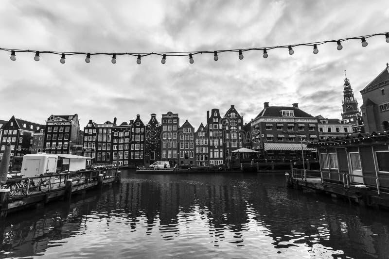 Amsterdam Nederländerna - December 12, 2009: Gamla byggnader längs den Damrak kanalen i Amsterdam royaltyfria bilder