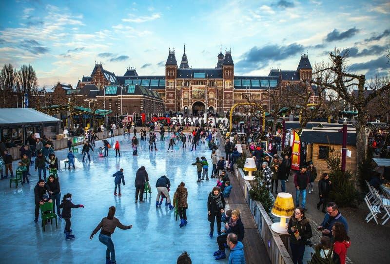 AMSTERDAM NEDERLÄNDERNA - JANUARI 15, 2016: Många personer åker skridskor på vinterskridskoåkningisbana framme av Rijksmuseumen,  royaltyfria foton