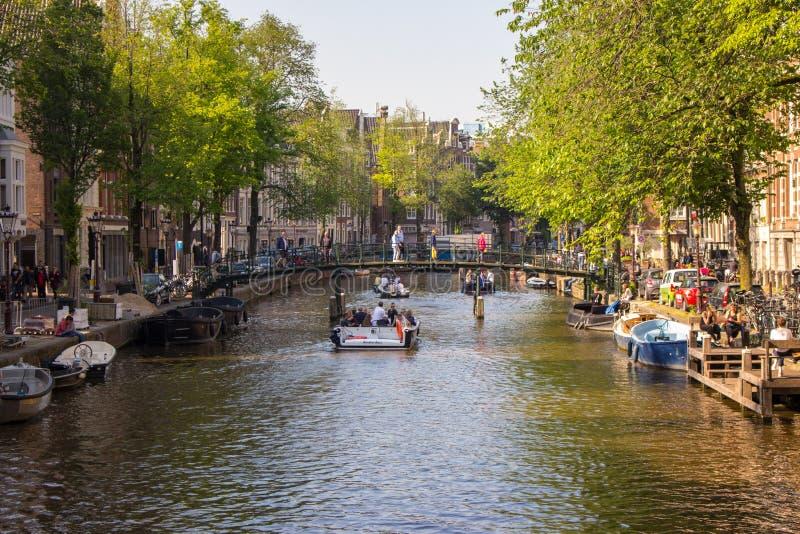 Amsterdam Nederländerna - 06/14/2019: kanal med bron och fartyg i Amsterdam, Nederländerna Traditionell holl?ndsk cityscape arkivfoton