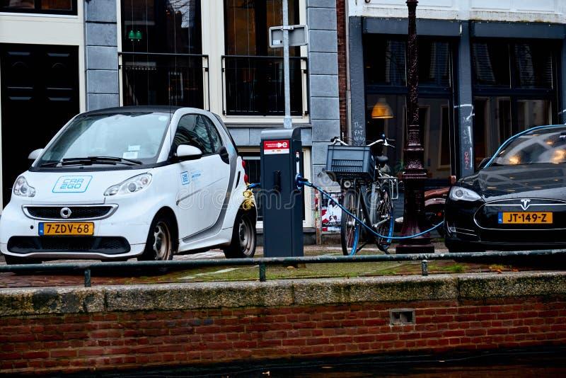Amsterdam Nederländerna - November 22, 2017: Strömförsörjning för elbiluppladdning bil som laddar den elektriska stationen arkivfoton