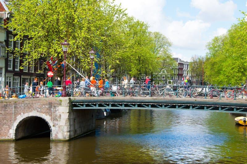 AMSTERDAM, 27 NEDERLAND-APRIL: Het kanaal van Amsterdam met menigte van mensen op de brug en fietsen op de Dag van de Koning in A stock fotografie