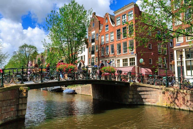 Amsterdam, Nederland - Augustus 3, 2017: Traditionele Nederlandse die fietsen op Hilletjesbrug-brug over Egelantiersgracht-kanaal royalty-vrije stock afbeelding