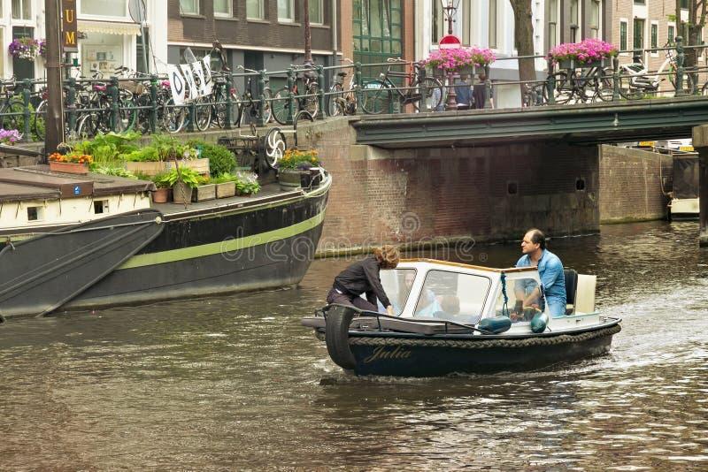 AMSTERDAM, NEDERLAND - JUNI 25, 2017: Kleine toeristenboot op één van de waterkanalen in het historische deel stock fotografie