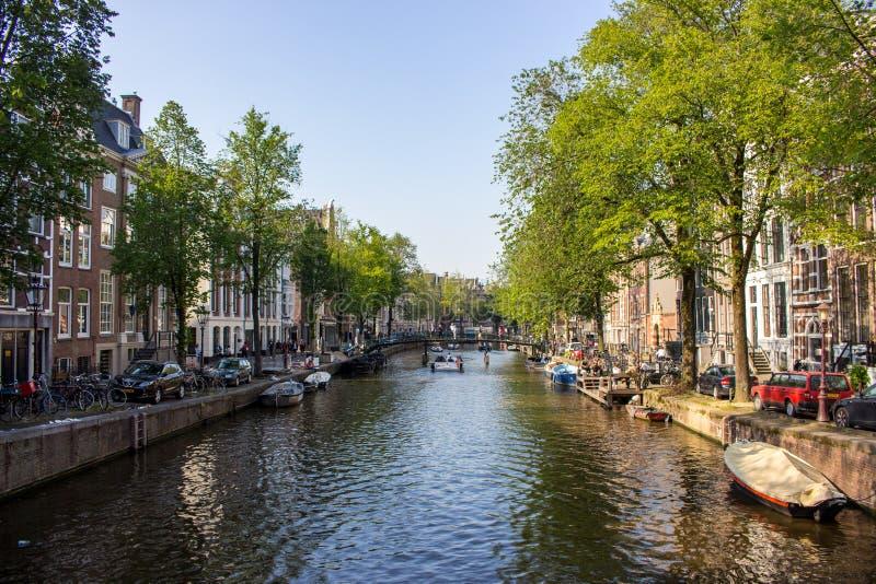 Amsterdam, Nederland - 06/14/2019: kanaal met brug en boten in Amsterdam, Nederland Traditionele Nederlandse cityscape stock afbeelding