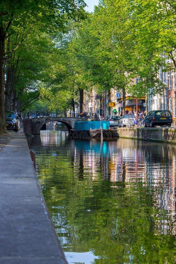 Amsterdam, Nederland - 06/14/2019: kanaal met brug en boten in Amsterdam, Nederland Traditionele Nederlandse cityscape stock foto's