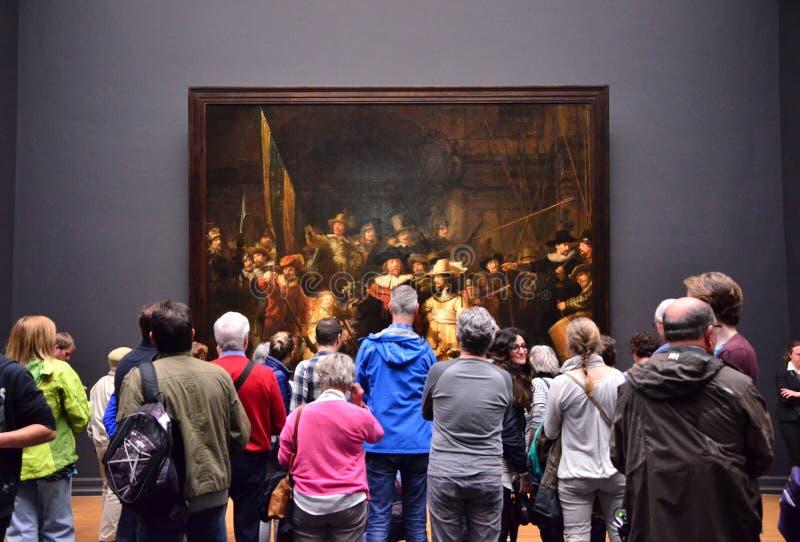 Amsterdam, Nederland - Mei 6, 2015: De bezoekers bij de beroemde het schilderen Nacht letten op in Rijksmuseum royalty-vrije stock afbeeldingen