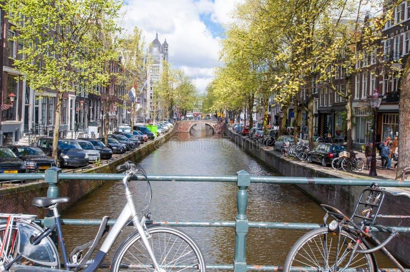AMSTERDAM NETHERLANDS-APRIL 27: Amsterdam kanal med cyklar på bron och de parkerade bilarna längs banken på April 27,2015 arkivfoton