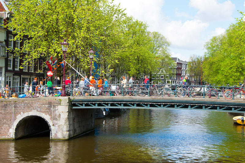 AMSTERDAM NETHERLANDS-APRIL 27: Amsterdam kanal med folkmassan av folk på bron och cyklarna på konungs dag i Amsterdam arkivbild