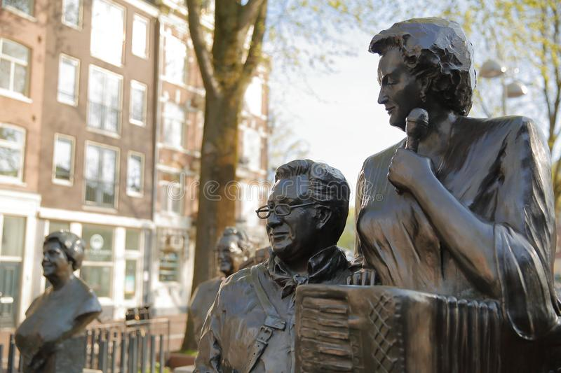 Bronze Sculpture of famous Dutch singer Jan Froger on the right, located on Elandsgracht close to Prinsengracht canal. AMSTERDAM, NETHERLANDS - APRIL 05, 2019 stock images
