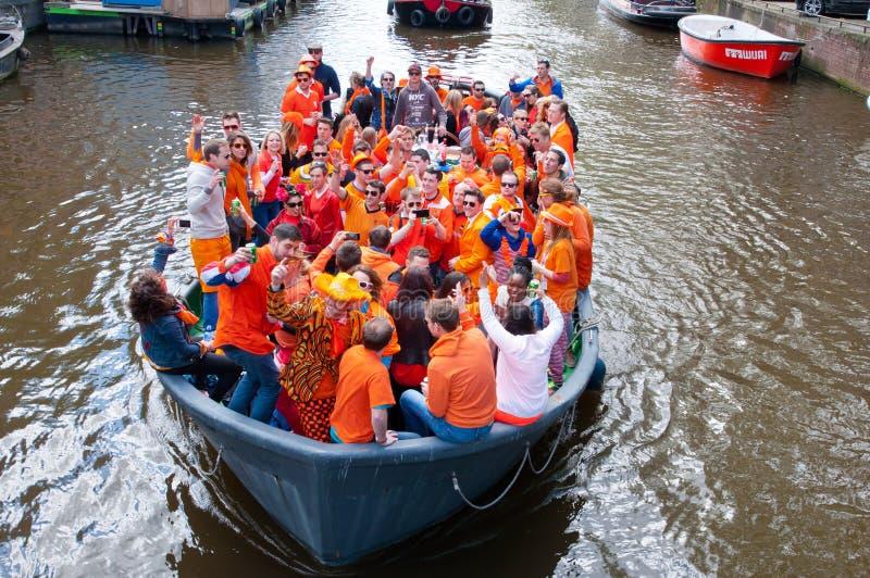 AMSTERDAM NETHERLANDS-APRIL 27: Folkmassan av den iklädda apelsinen för folk firar konungens dag i ett fartyg på April 27,2015 i  royaltyfria foton