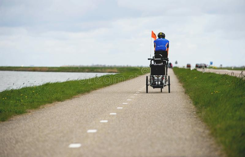 AMSTERDAM, NETHERLANDS, April 2017: Man on the Bike Pulling Baby Cart for a Bicycle Chariot by Thule. Bicycle path with Lake on royalty free stock photo