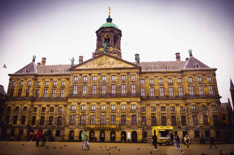 AMSTERDAM, NETHERLANDS, APRIL, 23 2018: Outdoor view of unidentified people walking at the Royal Palace on Dam Square in. Amsterdam. Built as city hall during stock images
