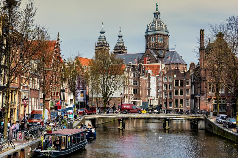 AMSTERDAM, NETHERLANDS - APRIL 10, 2018: St. Nicholas Church and Amsterdam canal with typical dutch houses. St. Nicholas Church is royalty free stock images