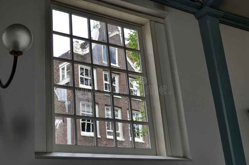 Amsterdam, the Netherlands. August 2019. Seen from inside the church of the city beguinage, through a large window one recognizes. The typical facades of Dutch royalty free stock photos