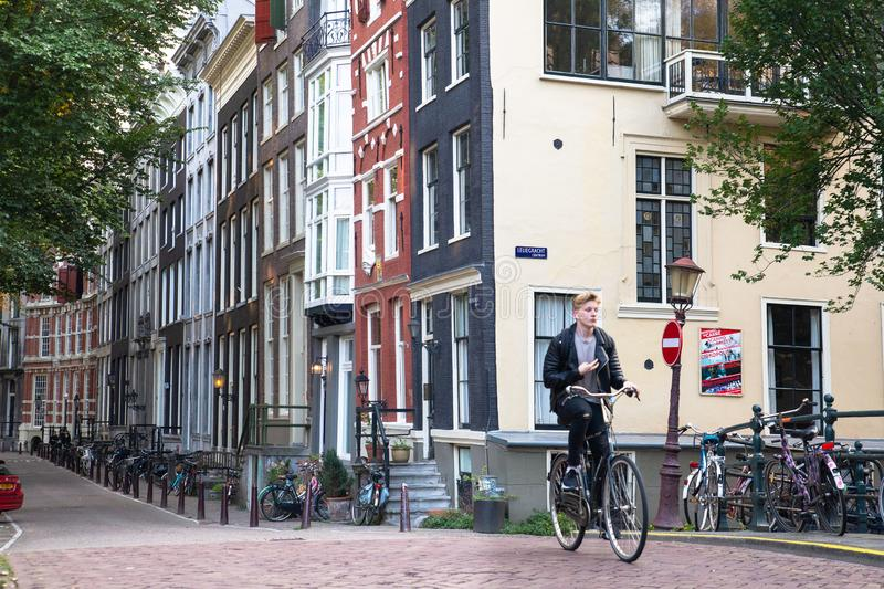 Street scene from Amsterdam with person riding a bicycle and typical architecture royalty free stock photo